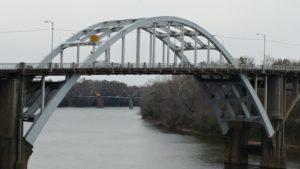 Schoolnik visiting the Edmund Pettus Bridge Selma, Alabama. Metal bridge over river on grey day.