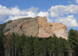 Crazy Horse Custer South Dakota. Giant mountain carving, with blue skies overhead and pine trees in foreground.