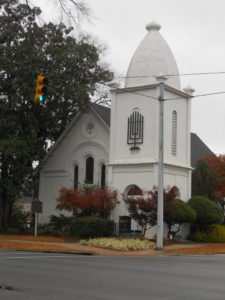Southern Synagogues: Temple Beth El Anniston Alabama. White building on street corner with menorah sculpture above front door.