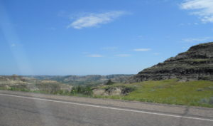 North Dakota Badlands. Roadway looking out on blue skies and rockbound hills.