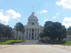 Schoolnik visiting the State Capitol Montgomery Alabama. Stately white building, with cupula with blue skies.