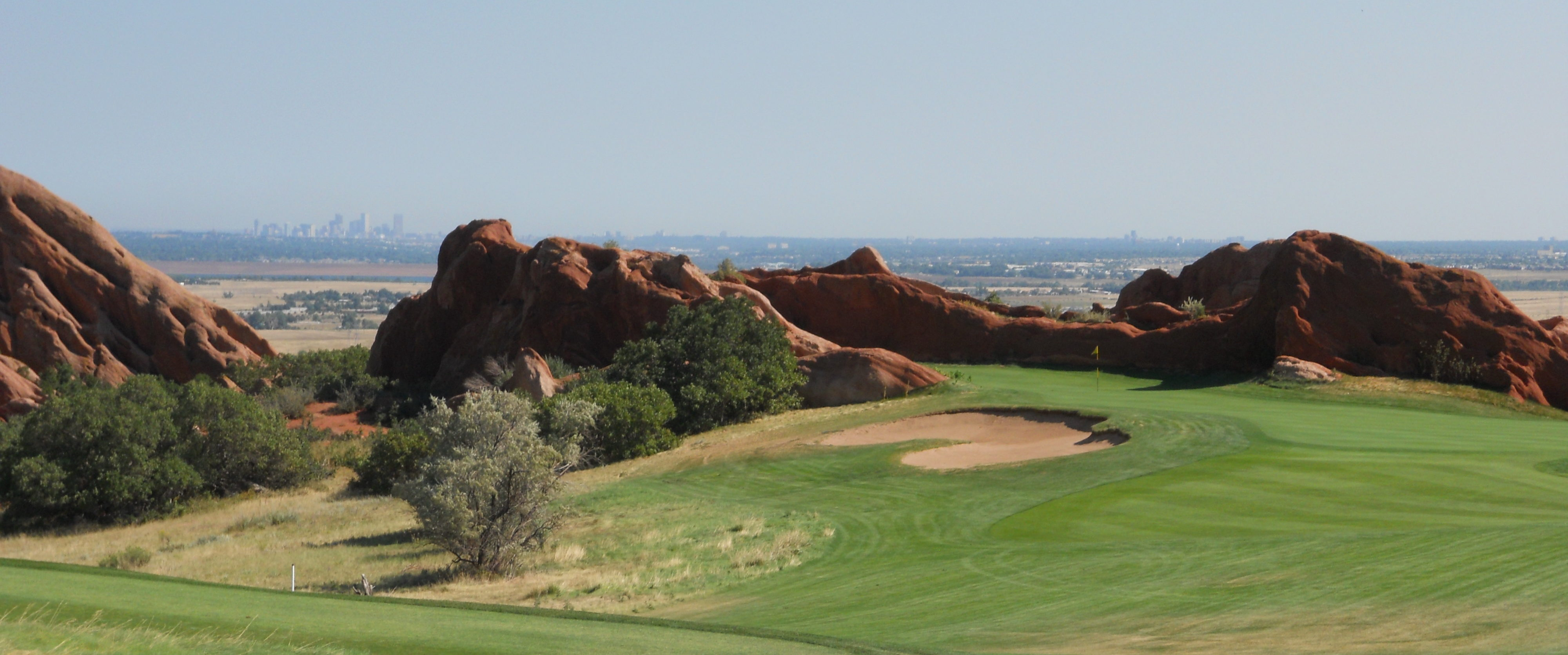 Arrowhead Golf Course, Littleton, Colorado. Golf course framed by red rocks with Denver sky line in distance.