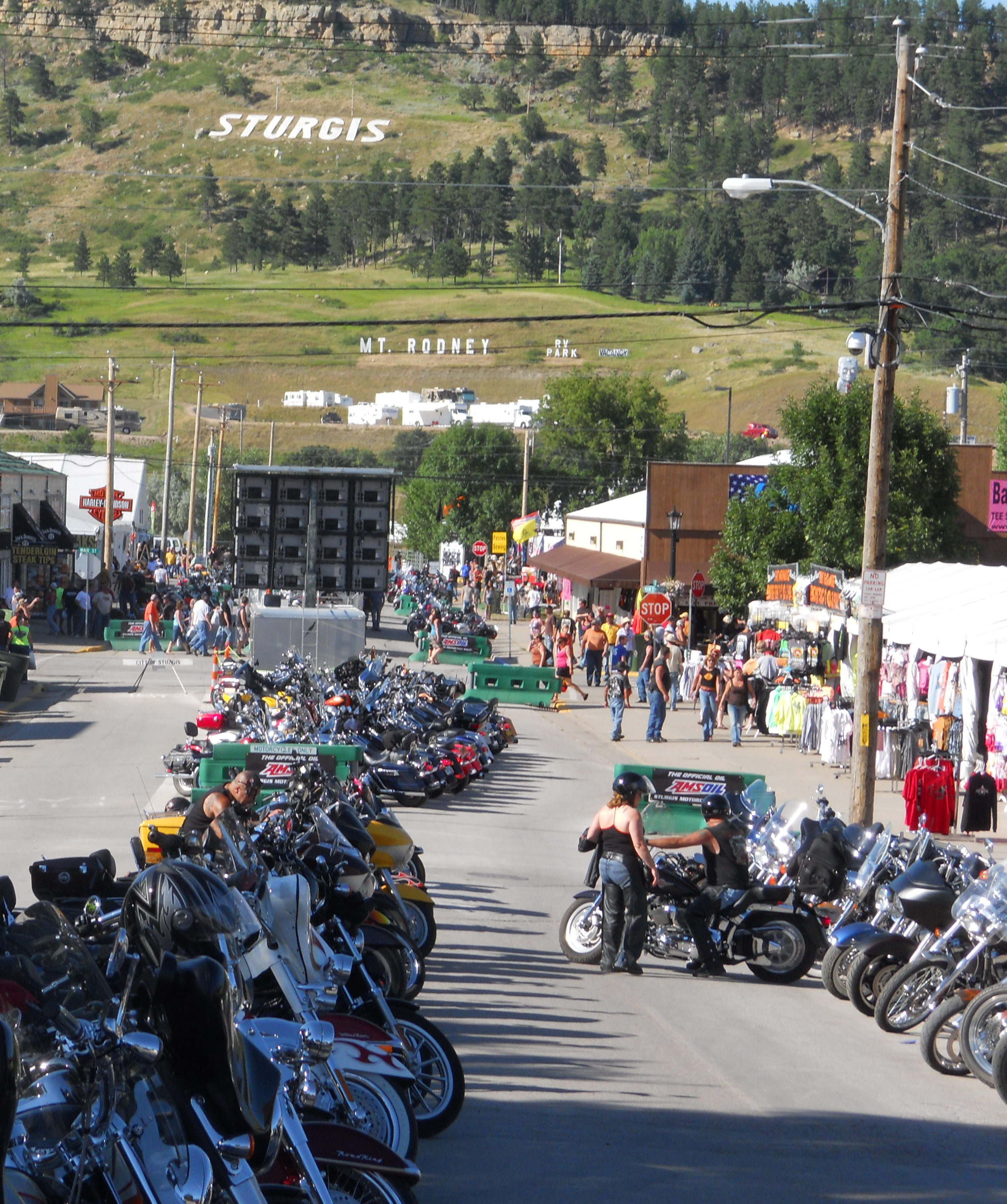 Sturgis Motorcycle Rally Sturgis, South Dakota. Row of motorcycles with Stugis sign on hill in distance